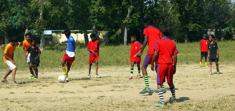 lapset pelaavat jalkapalloa Intiassa