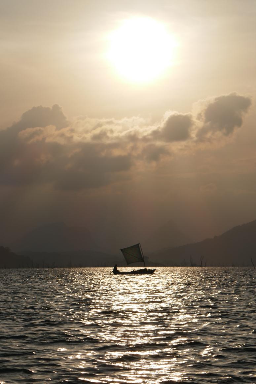 kalastajan vene lipuu auringonlaskuun Gal Oyan kansallispuistossa
